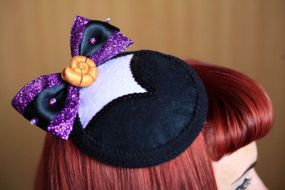 Circular fascinator inspired by Ursula the sea witch from The Disney film The Little Mermaid Soft felt base is comfortable to wear with pre attached clip for easy wear. Decorated with black and purple felt, black sequins and a glittery purple and black satin bow embellished with beads and sequins. Finished off with a gold polymer clay shell and black edging. The fascinator is approximately 5 inches wide. Any question please feel free to message me.   Please note shipping delay due to etsy…