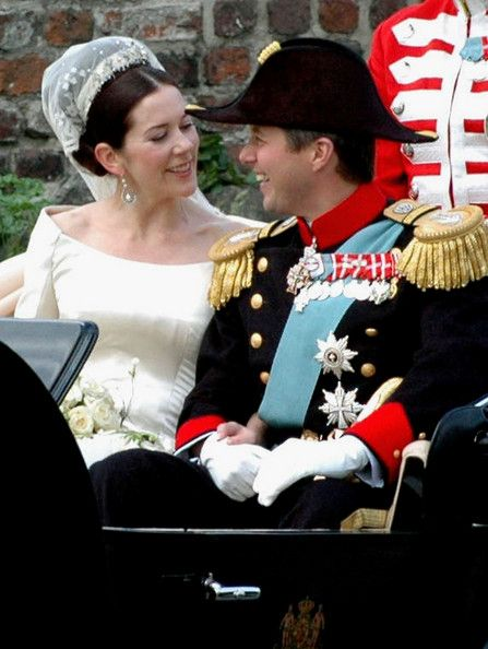 Danish Crown Prince Frederik and his bride Mary wave from their carriage during a procession from Copenhagen Cathedral to Amalienborg Palace May 14, 2004