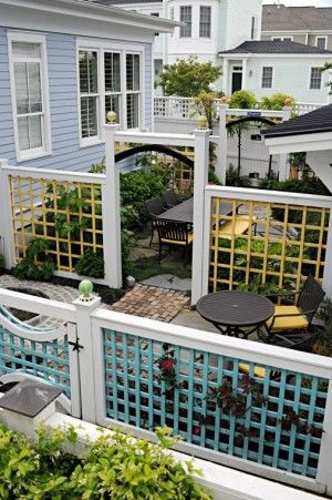 """Fences divide small yard into """"rooms"""". Curved gates allow small pets too pass through."""