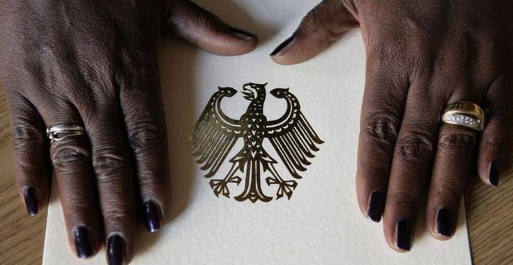 Die Hände einer Afrikanerin liegen auf der Einbürgerungsurkunde der Bundesrepublik Deutschland