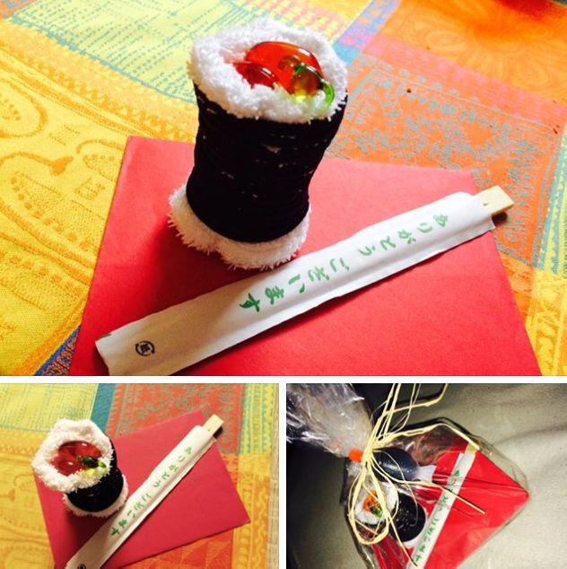 """Eine tolle Geschenkidee für Sushi-Liebhaber. Ein Gutschein mal anders.  Das """"Sushiröllchen"""" ist aus einem Waschlappen (weiß), Haargummis (schwarz) und Badepralinen (orange) gemacht."""