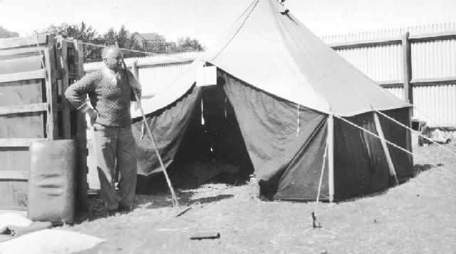 Temporary Shelter. View of a temporary shelter taken following the Hawke's Bay earthquake in 1931. An unidentified man stands to the left of the tent.  Photographer, unknown.