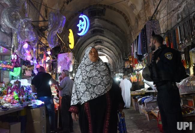 An Israeli police watches a Palestinian walk by decorations for the Muslim holy month of Ramadan at an exit from the Al-Aqsa Mosque…