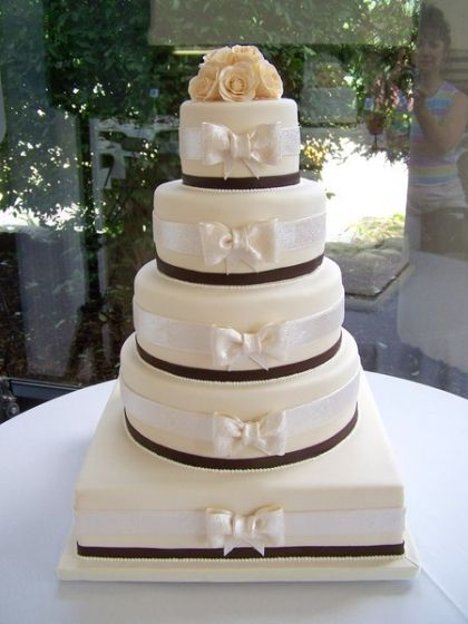 This stunning wedding cake featured ivory fabric bows on each tier and a cluster of gumpaste ivory roses on top.