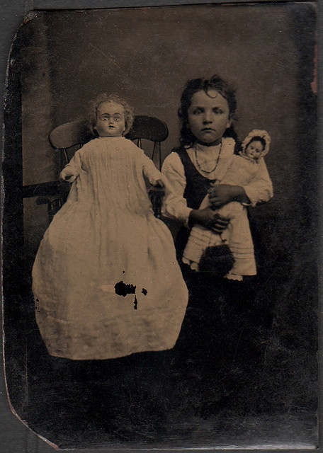 A very serious little girl posed beside a very creepy ...