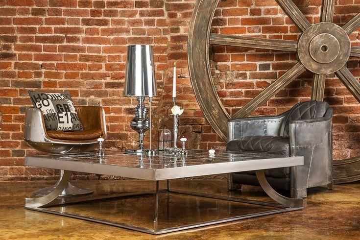 table basse industrielle en acier inox, fauteuils en cuir, roue de chariot décorative et lampe design