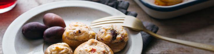 Verwijder de steeltjes van de champignons., Snijd de tomaten en olijven in kleine blokjes. Hak de basilicum en gepelde knoflook fijn., Meng doorheen het Soja Alternatief voor Plattekaas en voeg naar smaak zout toe., Bestrijk de champignons met olijfolie, vul ze met het mengsel en leg ze op een bakplaat., Bak 12-15 minuten in de oven op 200 °C. Ook koud lekker.