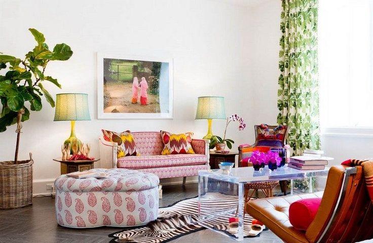petit salon blanc aménagé avec un canapé à motifs roses, ottomane en blanc à motif paisley rose, tapis zèbre, rideaux en blanc et vert et une figuier lyre