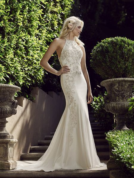 Casablanca Bridal Style 2243 - Camellia  With a breathtaking halter neckline and slimming sheath silhouette, Camellia is a gown designed for the trendy bride. Beading and sparkle decorates the bodice as well as the train, and a parade of buttons runs down the back, beginning at the open back just beneath the beaded straps.