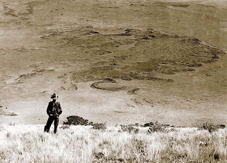 From the top of Capulin Mountain, circa 1909, this geologist stares out at congealed lava flows. Surveyors like him were instrumental in convincing the government to set it aside as a preserve in 1891, and eventually as the Capulin Volcano National Monument in 1916. Before him, Santa Fe Trail emigrants and traders crossed the plains in view of this rim, and even Charlie Goodnight's cattle trail passed under its shadow.