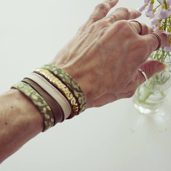 Bracciale realizzato a mano con nastro sbieco di cotone verde e tessuto di poliestere verde scuro e beige. Un nastro verde scuro è decorato da paillettes dorate. Chiusura con due bottoncini verde scuro e asole in cotone verde.  Lunghezza bracciale (escluse asole): 16 cm Larghezza bracciale: 4,5 cm  Tutte le creazioni C-Lab.Atelier sono fatte a mano con amore.  Grazie per la visita!  Guarda anche la collana e gli orecchini https://www.etsy.com/it/listing/215431563&#x2...
