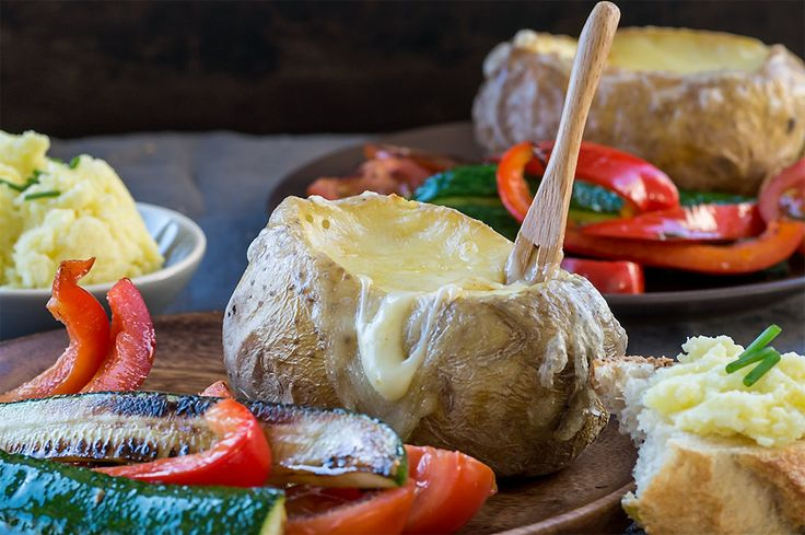 Gefüllte Ofenkartoffel mit geschmolzenem Ofenkäse und Gemüse zum Stippen, eine wunderbare Alternative zum Raclette oder Käsefondue.