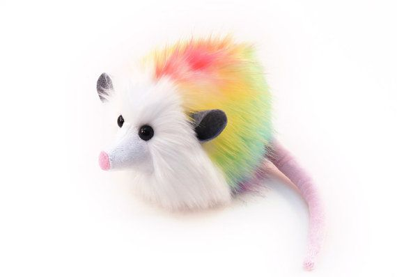 Hi, my name is Prism and I am a Fuzziggle. My fur looks like a rainbow spilled all over me. Im a medium size opossum, about 5 x 5 x 8 inches.  Im made