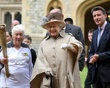 This image made available by LOCOG shows Queen Elizabeth II, center, and the Duke of Edinburgh, obscured, and Olympic chairman Sebastian Coe right, watch as Torchbearer 073 Gina Macgregor, left, holds flame....
