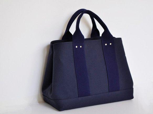大人のカジュアルスタイルに6号帆布の丈夫なトートバッグ。単色使いでカジュアルないつもの帆布バッグがワンランク上の印象です。手荷物に応じてサイドのホック調整で横長トートにも。ホックを外せば横向きA4ファイルが無理なく収納。大変丈夫な6号トートバッグですが、たっぷりの手荷物にも中敷付きで,更に強度もアップ。用途に合わせて変化も楽しめる頼もしい上品トートバッグです。※サイズをよく確認の上ご注文ください。国産素材にこだわり生産しています。サイズ:W35cm~45cm H24cm D16cm 内側ポケット1ヶ所 素材 :綿 ナイロンテープ ホック/カシメ…