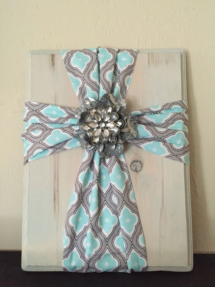 Fabric cross on wood. Super simple and easy to make. Fabric is gathered in the centers with a twist tie and stapled in the back. The centerpiece is made with two large embellishments from Hobby Lobby hot glued together on an alligator clip.