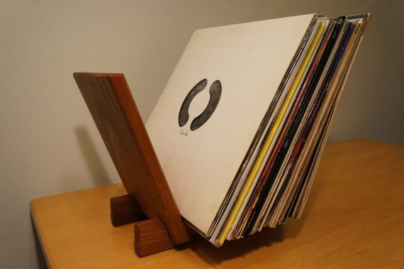 Wooden record stand, handcrafted in West Yorkshire. Made from solid West African Sapele, a dark Mahogany type wood with a reddish tint. It has a layered wavy grain in which the different layers reflect the light at different angles - truly beautiful. Holding up to 40 records, the angled panels of this beautiful piece make flip through browsing a breeze. Each stand is finished with 3 coats of Danish Oil.  Dimensions: 10 x 9 x 12   International shipping available please contact me for prices…
