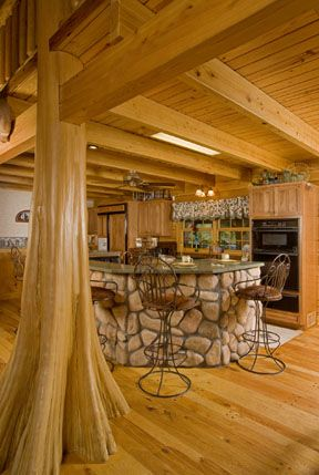 love the idea of using big tree trunks throughout the house for support. it just adds to the cabin. love the stone island too.