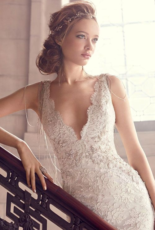 Ivory/Silver alencon lace trumpet bridal gown, V-neckline with beaded necklace at back, jeweled appliques at natural waist, chapel train. Style LZ3501 by JLM Couture, Inc.