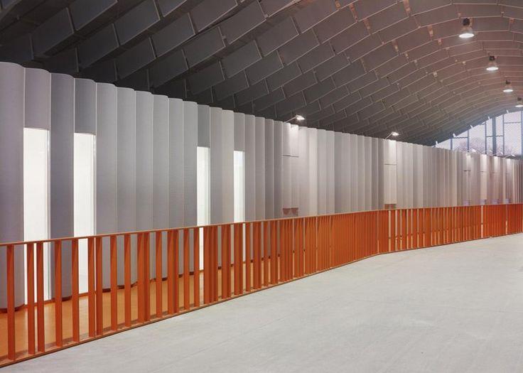 Bang Architectes has converted a former peanut factory in Calais into a skateboarding park with a bright orange mesh facade (photos by Julien Lanoo).