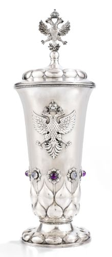 A Russian gem-set silver presentation cup and cover, Morozov, Petrograd, dated 1917. The flared body applied at the front with the Imperial eagle, the reverse with the civic arms of Petrograd above engraved inscription in French 'The Duma of Petrograd/ to S[on]. E[xcellence]. M[onsieur]. G[aston]. Doumergue/ 4/17 February 1917', above cabochon amethyst and moonstone-set stylised flowers, the lower body, base and lid with lobes, Imperial eagle finial.