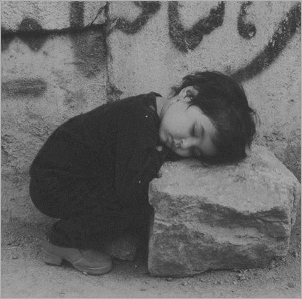 Exhausted Syrian child ĉollapsed in the rubble