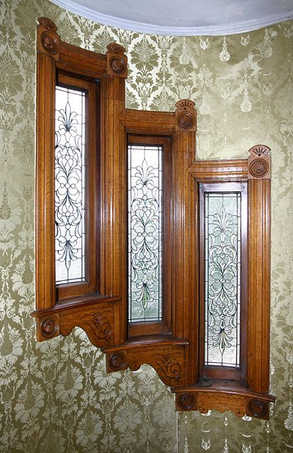 Amazing Windows with rosettes and Damask wallpaper. ~look like they are on the stairwell hall