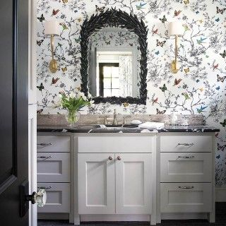 """The wallpaper sets the scene in the guest bathroom bringing in a little bit of nature. The """"Lillian"""" mirror by Made Goods also adds to the garden appeal. 