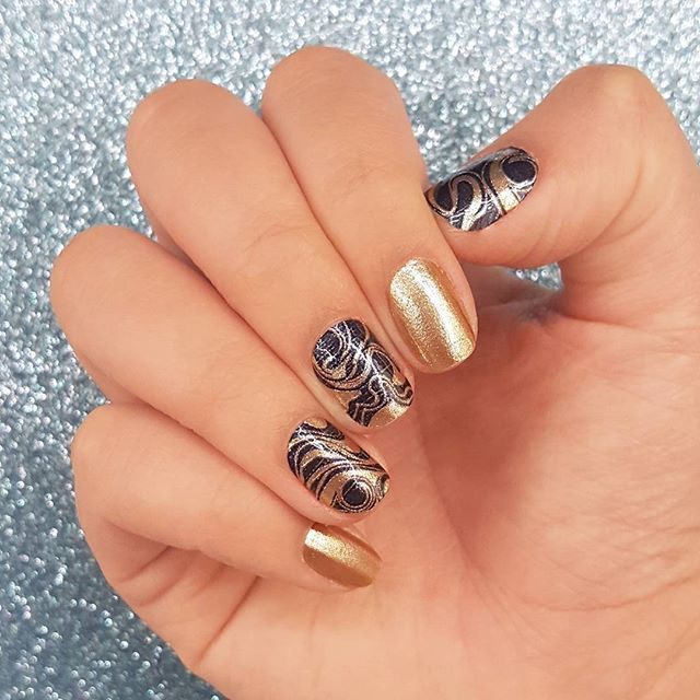 """The deep teal marble and shimmery gold of """"Zero Gravity"""" make a perfect pair. Explore this swirling nail art and more at incoco.com! #incoco #nailart #galaxynails #marblenails"""