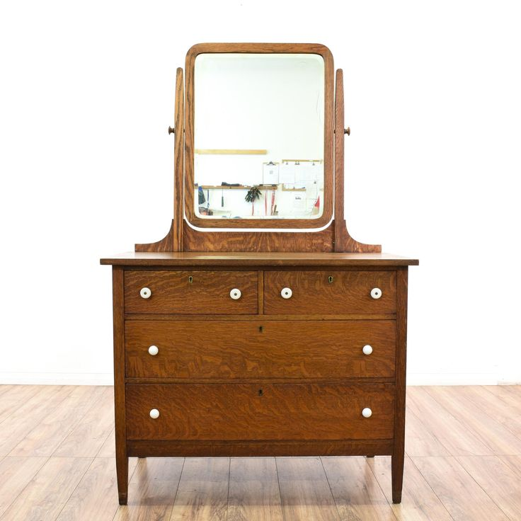 This antique vanity dresser is featured in a solid wood with a gorgeous tiger oak finish. This short dresser has 4 drawers, a curved swivel top mirror and white drawer pulls. Stunning piece perfect for a small bedroom! #americantraditional #dressers #vanitydresser #sandiegovintage #vintagefurniture