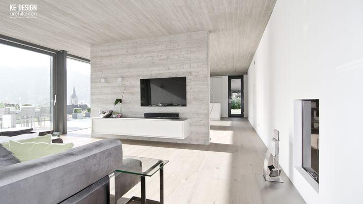 offenes Wohnzimmer mit Sichtbetonwand und Decke in Brettschaloptik, sowie einem herrlichen Weitblick übers Tal. Der Kamin ist in die Wand integriert.