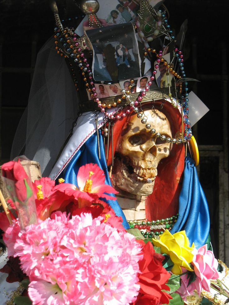 A depiction of Nuestra Señora de la Santa Muerte, a popular folk saint (that is to say a saint in Folk Catholicism, but not actually canonized) and patron of fucking everything (that was a sarcastic exaggeration)... seriously, look up what she's a patron of. I literally couldn't fit it in this pin description.