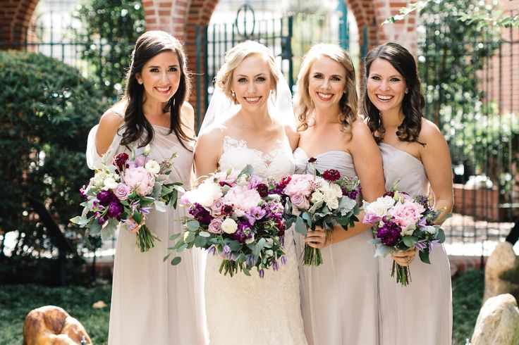 bride and her bridesmaids in pale grey gowns carry their bouquets of light pink peony, ocean song rose, dark purple stock, dried lavender, light pink ranunculus, lavender lisianthus, dusty miller, burgundy scabiosa, pink wax flower, white majolik spray rose, bay leaf, fern, silver dollar eucalyptus & vines wrapped in cream satin ribbon