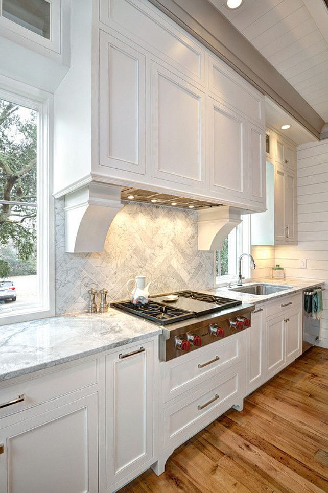 South Carolina Elevated Beach Houseshiplap, tongue and groove and plank walls. custom hood with the corbels in this kitchen. Also, notice the marble backsplash set in a herringbone pattern.
