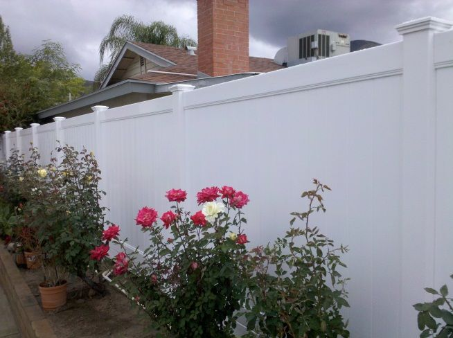 Planting Colorful Flowers Against White Vinyl Fences Makes A Landscaping Yard View