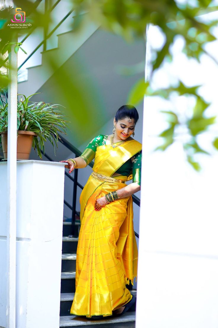 Saree -Traditional bride with rich mango yellow kanchipuram silk saree design with traditional check design with vibrant contrast green colour traditional border merges well and brings the bride saree in to rich traditional style. Blouse - Contrast green colour out fit is designed with small flower design arri is excellent complimentary for the bride saree.