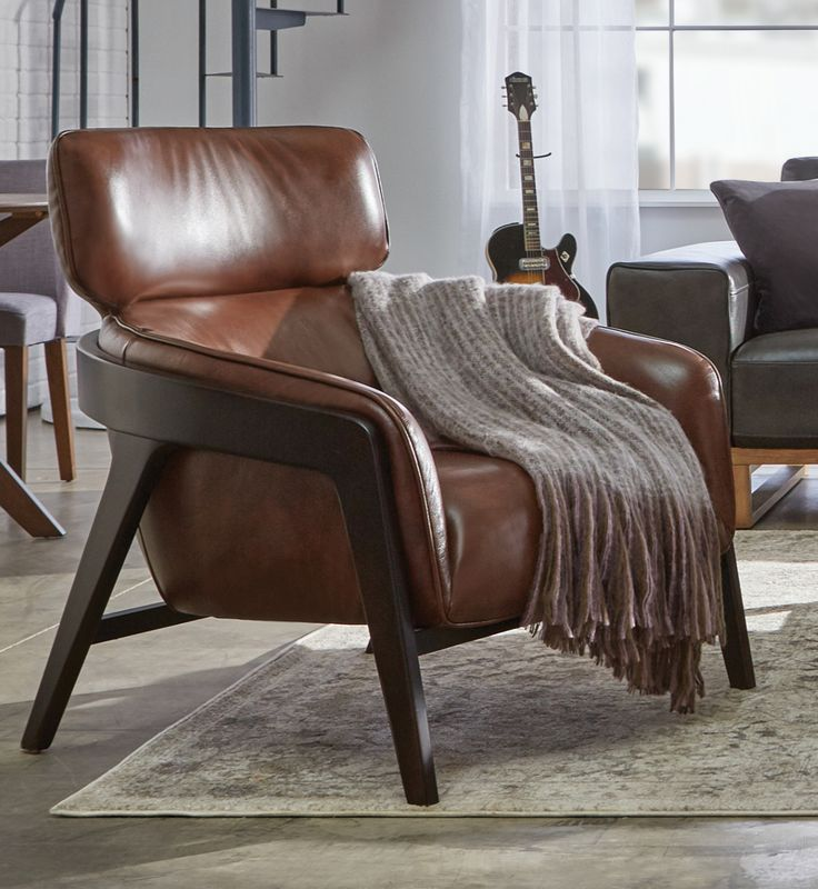 This gorgeous leather chair is all retro good looks with its Mid-Century style.  The wrap-around wood arms add an extra splash of panache, ensuring it will become a showpiece in any living room, family room or bedroom. Pairs well with Casual or Modern home decor.
