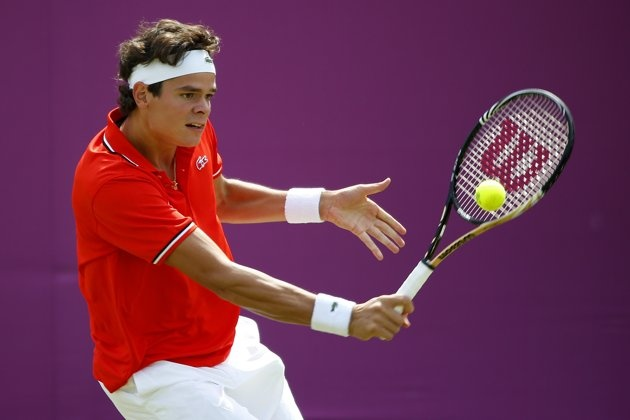 Milos Raonic of Canada plays a backhand during the Men's Singles Tennis match against Tatsuma Ito of Japan on Day 3 of the London 2012 Olympic Games at the All England Lawn Tennis and Croquet Club in Wimbledon on July 30, 2012 in London, England.