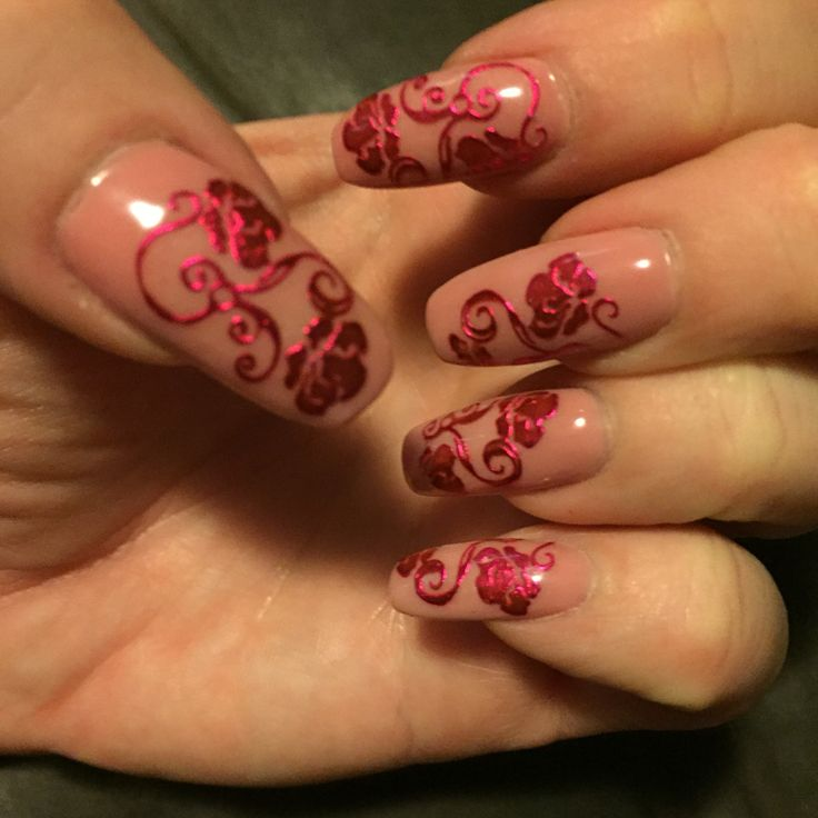 Nude pink acrylic nails with pink nail art.