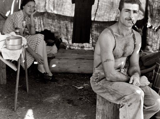 "Oregon, August 1939. ""Unemployed lumber worker goes with his wife to the bean harvest. Note Social Security number tattooed on his arm."" View full size 