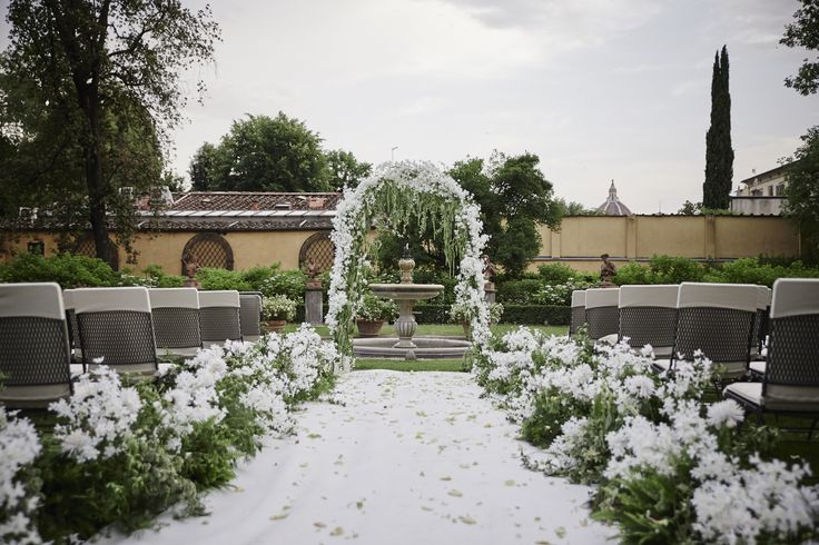 White enchanted wedding aisle with greenery and flower decorated arch, Duomo View garden