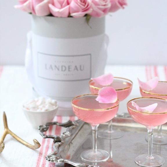 Des roses décoratives avec 4 coupes vintage remplie d'un cocktail rose au champagne