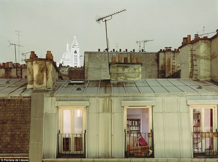 A woman sits on her couch with her floor-to-ceiling windows wide open on what appears to be a warm Paris night .