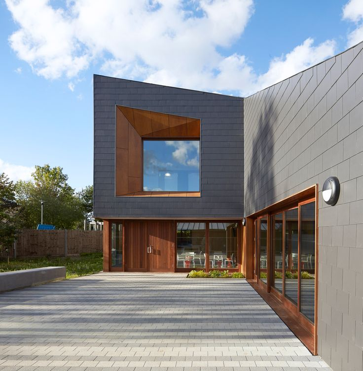 Recessed windows set into the facades of this youth centre feature faceted timber-lined frames that contrast with the building's dark fibre-cement cladding