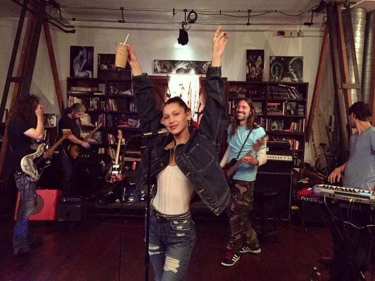 Bella Hadid shared an Instagram of her wearing a denim on denim look while posing with a friend's band.