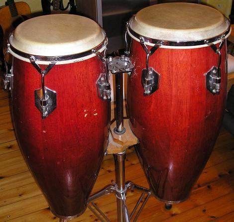 CONGA. La conga, tambó o tumbadora, es un instrumento membranófono de percusión de raíces africanas, que fue desarrollado en Cuba. La conga tiene su origen en los tambores africanos hechos a partir de un tronco sólido ahuecado y con una piel clavada sobre la abertura de un extremo. El tambor de makuta, de origen bantú, ha sido identificado como un posible antepasado. Otro antiguo nombre dado por los nativos africanos a este instrumento fue «tahona». Luego se le llamó «tumba», palabra…