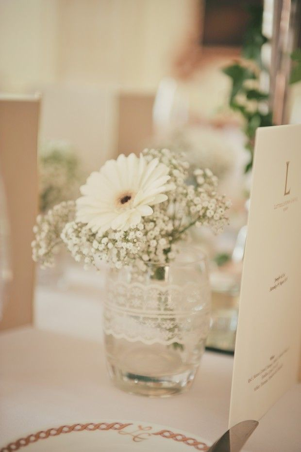 Baby's breath and gerbera daisies in glass centerpiece. Maybe just one purple daisy or white? One of each?