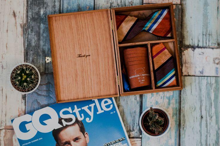 Flatlay mit GQ Style und accessory box von Gentleman's Agreement. Das perfekte Geschenk für modebewusste Männer.  Die Herren Accessoire Box besteht aus einer Fliege, einem Einstecktuch und einem Paar Socken. Die Accessoires sind alle perfekt aufeinander abgestimmt.