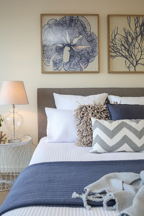 Shabby chic, coastal, beach style, Hamptons, master bedroom, waffle bedding, navy blue throw rug, navy blue cushion, chevron cushion, upholstered bed head, glass lamps, large round white side tables, coral artwork: