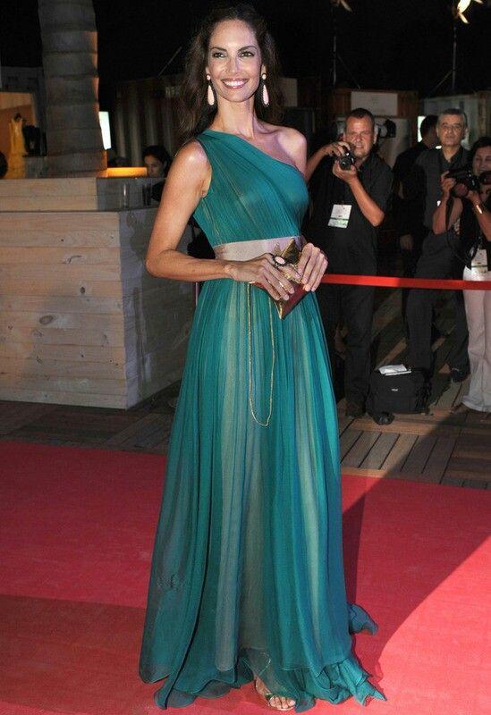 Vestido largo verde con escote asimétrico y corte griego, accesorios dorados.